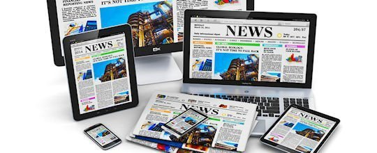 Modern computer media devices concept: desktop monitor, office laptop, tablet PC and black glossy touchscreen smartphones with internet web business news on screen and stack of color newspapers isolated on white background