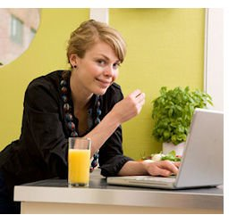 A female smiles at the camera while eating halthy lunch and using the computer